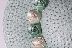 Un sombrero femenino de ala ancha es verde claro, adornado con las flores hechas en casa Flores de la tela bajo la forma de rosas Fotos de archivo