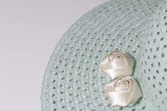 Un sombrero femenino de ala ancha es verde claro, adornado con las flores hechas en casa Flores de la tela bajo la forma de rosas Foto de archivo