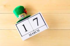Un sombrero verde en una tabla de madera Día de s de StPatrick ' Un calendario de madera que muestra el 17 de marzo Foto de archivo