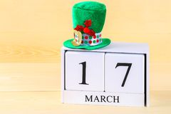 Un sombrero verde en una tabla de madera StPatrick \ 'día de s Un calendario de madera que muestra el 17 de marzo Foto de archivo libre de regalías