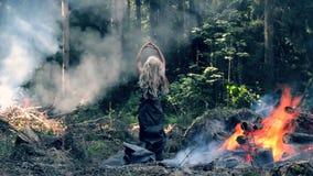 Un soporte de la mujer joven cerca del fuego y de los aumentos sus manos y los baja metrajes