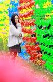 Un soporte de la mujer joven delante de los molinoes de viento coloridos imagenes de archivo