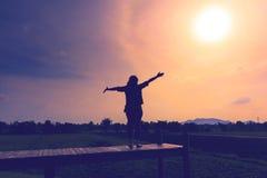 Un soporte feliz de la mujer arma para considerar el sol Fotos de archivo