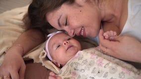 Un sourire de famille dans le lit, o? regards de maman, contacts et entretiens avec sa petite fille banque de vidéos