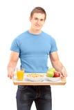 Un sourire portant un plateau en bois avec les boissons et la nourriture Photos libres de droits