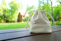 Un special et un sac blanc de mode sur une table en bois Image stock