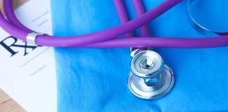Un stéthoscope formant un coeur et un presse-papiers sur un uniforme médical, plan rapproché Photo stock