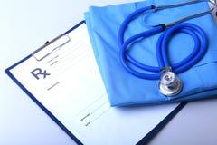 Un stéthoscope médical et la prescription de RX se trouvent sur un uniforme médical Images stock