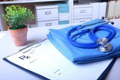 Un stéthoscope médical et la prescription de RX se trouvent sur un uniforme médical photos stock