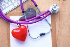 Un stéthoscope médical se trouve sur les antécédents médicaux patients du ` s sur un fond d'ordinateur Le concept des soins médic Photos libres de droits