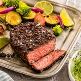 Un steak au poivre grillé garni avec le citron, l'oignon et frais elle image stock