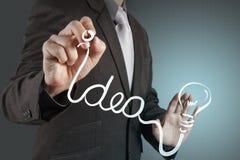 Un stylo dessinant l'ampoule Photographie stock libre de droits
