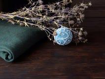 Un suéter verde caliente, flores secadas y una mentira azul de la bola de la Navidad en la tabla de roble Fotos de archivo libres de regalías