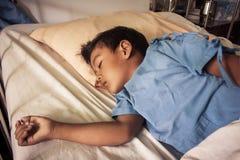 Un sueño enfermo del pequeño muchacho asiático en la cama en el hosital Imagenes de archivo