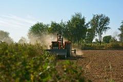 Un suolo di lavorazione dell'agricoltore per la preparazione del letto di semina con una macchina 'Rotary del tiller' di Rota Fotografie Stock Libere da Diritti