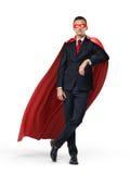 Un super héroe en un traje de negocios y un cabo rojo que se inclinan en un objeto invisible en el fondo blanco fotografía de archivo libre de regalías