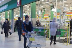 Un supermercado, hombre con un carro vacío, trabajador, editorial foto de archivo libre de regalías