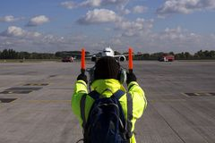 Un supervisor ayuda en el estacionamiento de los aviones foto de archivo