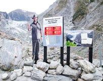 Un support de photo d'homme montre le règlement de panneau d'avertissement pour la chute de glace, chute de roche, l'inondation,  photo libre de droits