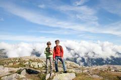 Un supporto di due ragazzi sulla cima in alta montagna Immagine Stock