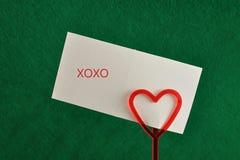 Un supporto di nota con un cuore rosso con una nota fotografie stock