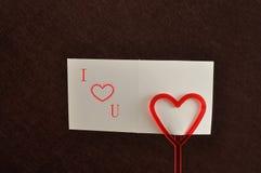 Un supporto di nota con un cuore rosso con una nota immagini stock libere da diritti