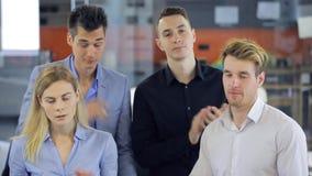 Un supporto di quattro impiegati di concetto nella sala per conferenze e nell'applauso archivi video