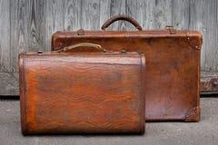 Un supporto di viaggio di due valigie vicino ad un garage Immagini Stock Libere da Diritti
