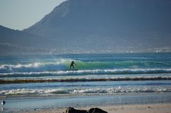 Un surfer montant une vague entourée par des montagnes, Cape Town, Afrique du Sud photo stock