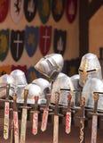 Un surtido de cascos, de escudos y de espadas Fotos de archivo