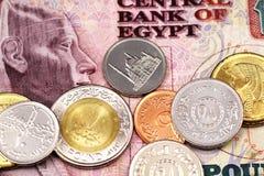 Un surtido de monedas egipcias en una nota egipcia de diez libras fotografía de archivo libre de regalías