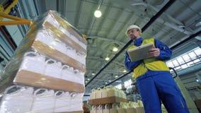 Un surveillant observe des récipients en plastique obtenir enveloppé dans la cellophane banque de vidéos