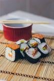 Un sushi fijó con los palillos del cuenco y del bambú de la salsa en el fondo de bambú Imagen de archivo libre de regalías