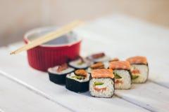 Un sushi a placé avec des bâtons de bol et de bambou de sauce sur le fond blanc Photos stock