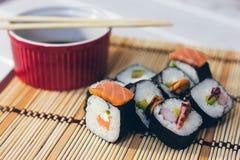 Un sushi a placé avec des bâtons de bol et de bambou de sauce sur le fond en bambou Image libre de droits