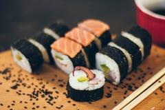 Un sushi a placé avec des bâtons de bol et de bambou de sauce sur le fond noir sur le conseil en bois Image libre de droits