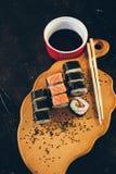 Un sushi a placé avec des bâtons de bol et de bambou de sauce sur le fond noir sur le conseil en bois Photo stock