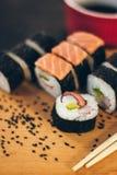 Un sushi a placé avec des bâtons de bol et de bambou de sauce sur le fond noir sur le conseil en bois Photos stock