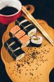 Un sushi a placé avec des bâtons de bol et de bambou de sauce sur le fond noir sur le conseil en bois Photographie stock