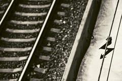 Un suspiro eléctrico del peligro amonestador y la pista ferroviaria en el negro Imagen de archivo