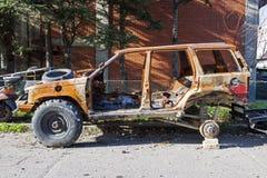 Un suv oxidado quemado del coche del camino en la calle Fotografía de archivo