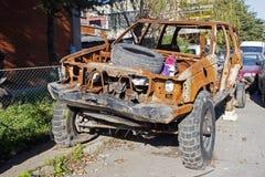 Un suv oxidado quemado del coche del camino en la calle Imagen de archivo libre de regalías