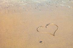 Un symbole de coeur écrit dans le sable Photo stock