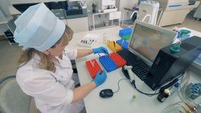 Un técnico de laboratorio mueve las muestras de sangre que hacen exámenes médicos en laboratorio moderno metrajes