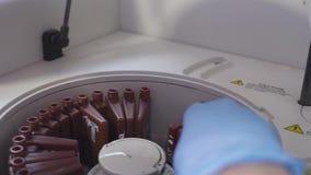 Un técnico de laboratorio que hace un análisis de sangre carga los tubos en la máquina El ayudante que carga el frasco en el labo almacen de video