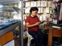 Un técnico del teléfono trabaja en un smartphone en su tienda en la ciudad de Antipolo Imagen de archivo libre de regalías