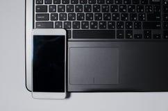 Un téléphone blanc se repose sur un clavier d'ordinateur portable Photos stock