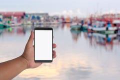 un téléphone de prise de main au-dessus des beaucoup petit bateau de pêche dans le port images stock