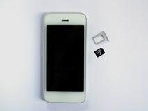 Un téléphone intelligent blanc, un bac à cartes de sim et un petit papier simulés As Images libres de droits