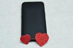 Un téléphone intelligent montré avec deux coeurs rouges de scintillement Photos libres de droits